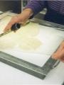 Le feuillet est positionné sur table lumineuse entre deux voiles de mylar. Les voiles de mylar sont appuyés sur le document à l'aide d'une spatule. Ils ne doivent présenter aucun pli de surface